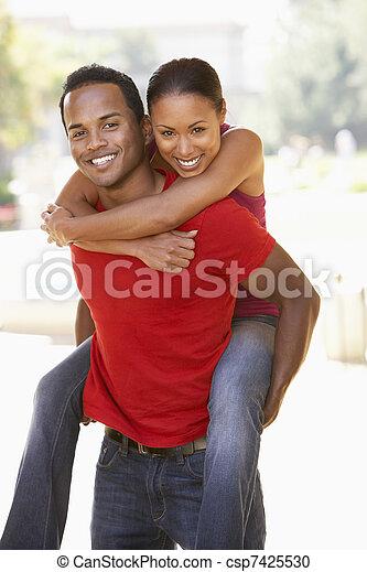 Young Man Giving Woman Piggyback Outdoors - csp7425530