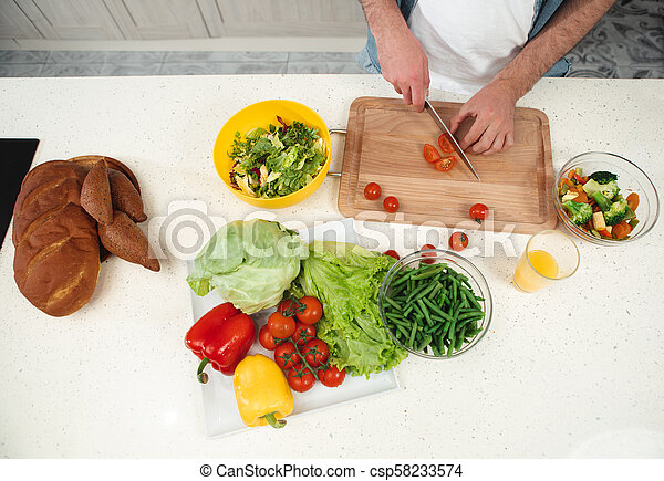 Young man hands cutting ingredients for salad - csp58233574