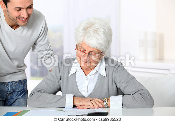 Young man helping elderly woman with paperwork - csp9985528