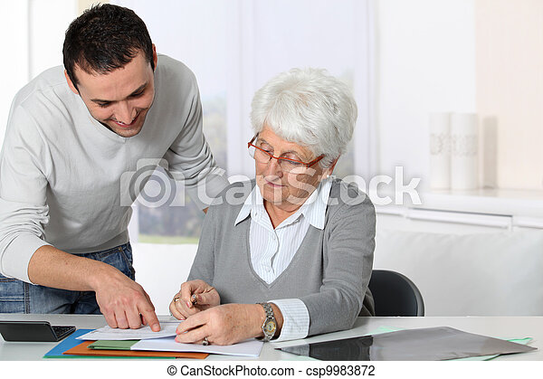 Young man helping elderly woman with paperwork - csp9983872