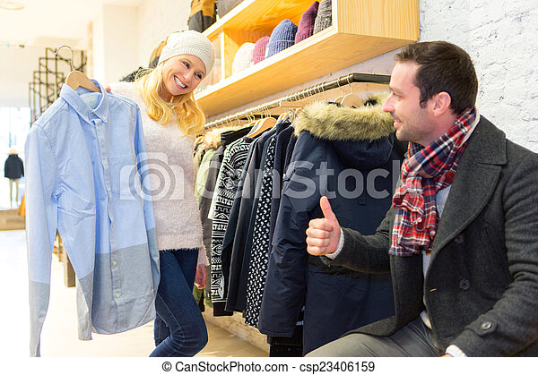 Young man helping his wife to choose clothes - csp23406159