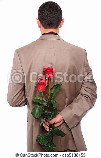 young man hides behind a rose - csp5138153