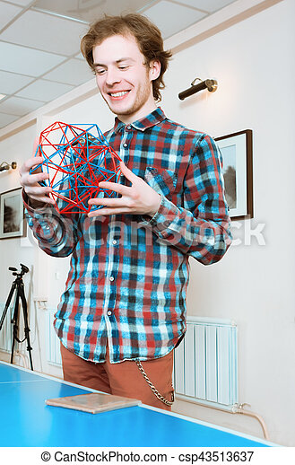 Young Man Holding The Volumetric Model Of Geometric Solid - csp43513637