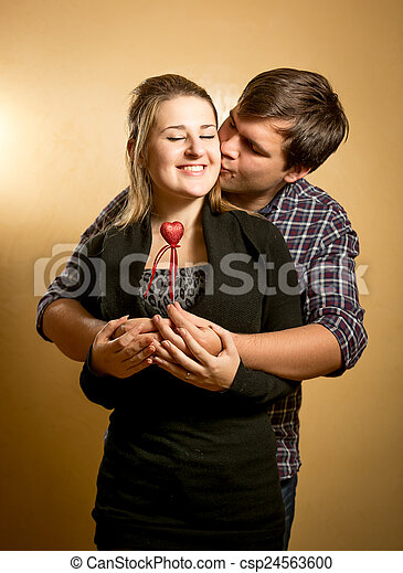 handsome young man hugging girlfriend from back and kissing in cheek