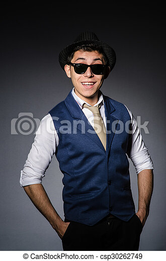 Young man in blue vest and hat against gray - csp30262749