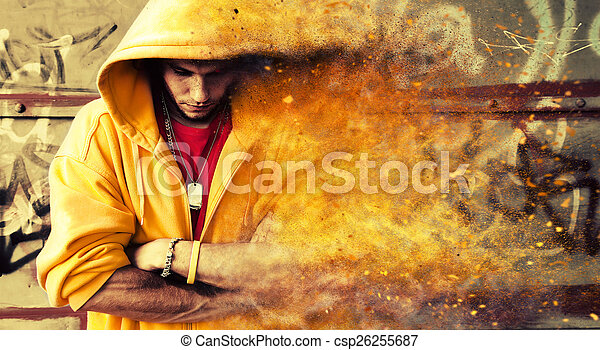 Young man in hooded sweatshirt on grunge wall. Particles effect - csp26255687