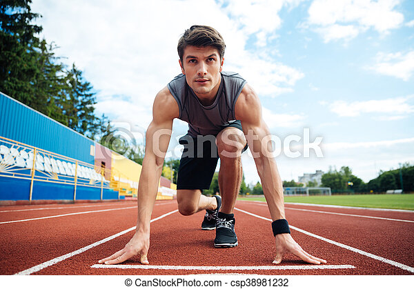 Young man in starting position for running on sports track - csp38981232