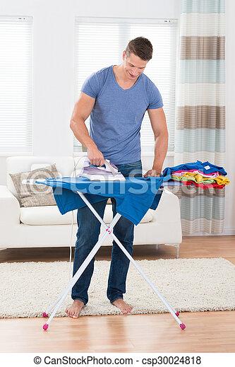 Young Man Ironing Clothes - csp30024818