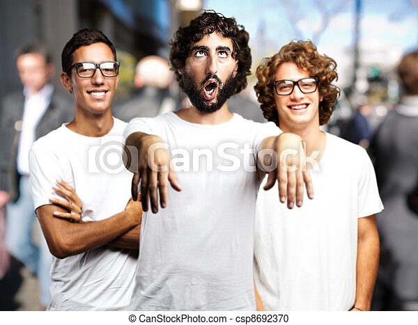young man joking with friends at crowded place - csp8692370