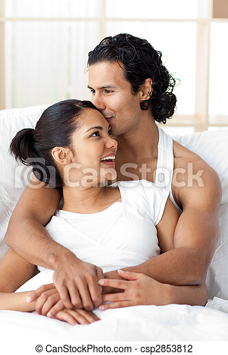 Young man kissing his girlfriend lying on the bed - csp2853812
