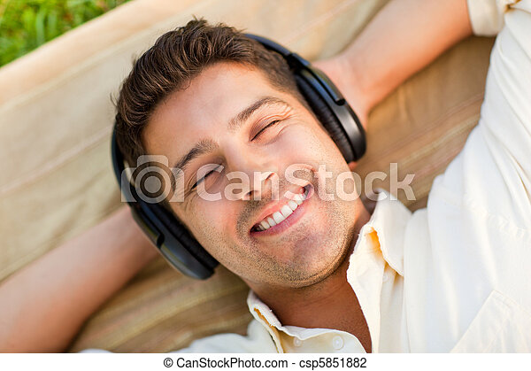 Young man listening to music in the park - csp5851882