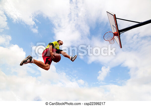 Young man making a fantastic slam dunk playing streetball, basketball - csp22399217