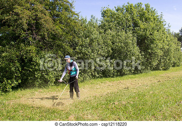 young man mowing the grass - csp12118220