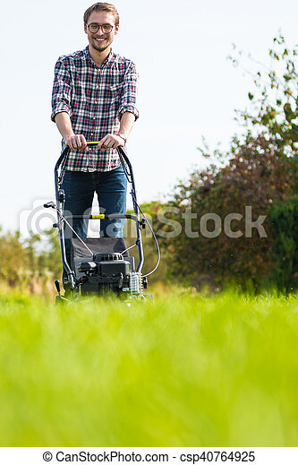 Young man mowing the grass - csp40764925