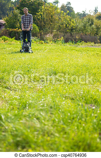 Young man mowing the grass - csp40764936