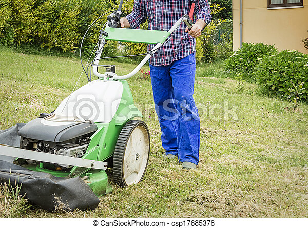 Young man mowing the lawn with a lawnmower - csp17685378