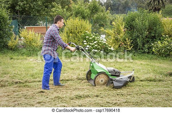 Young man mowing the lawn with a lawnmower - csp17690418
