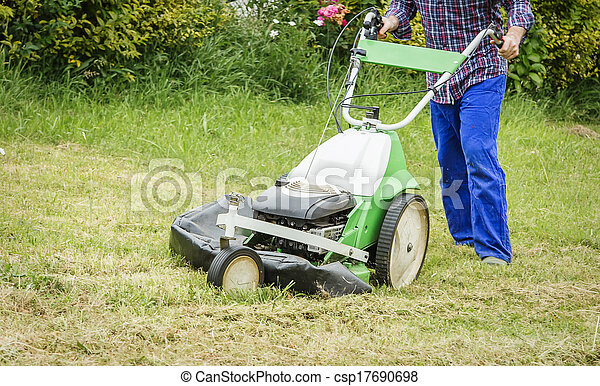 Young man mowing the lawn with a lawnmower - csp17690698