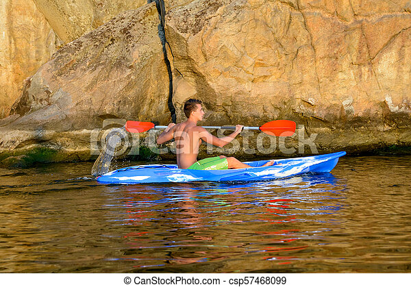 Young Man Paddling Blue Kayak on Beautiful River or Lake under High Rock in the Evening - csp57468099