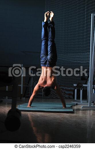 young man performing handstand in fitness studio - csp2246359