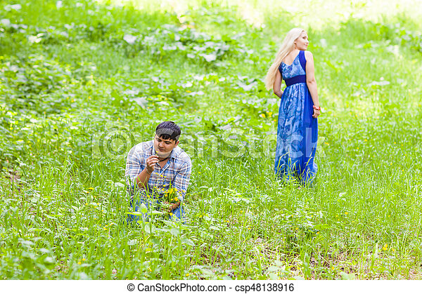 Young man picking up flowers for his woman - csp48138916