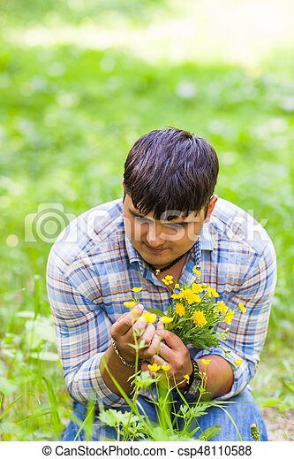 Young man picking up flowers for his woman - csp48110588