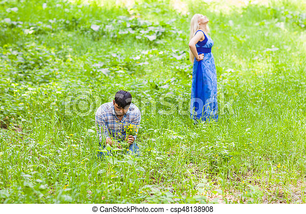 Young man picking up flowers for his woman - csp48138908