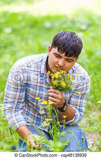 Young man picking up flowers for his woman - csp48138939