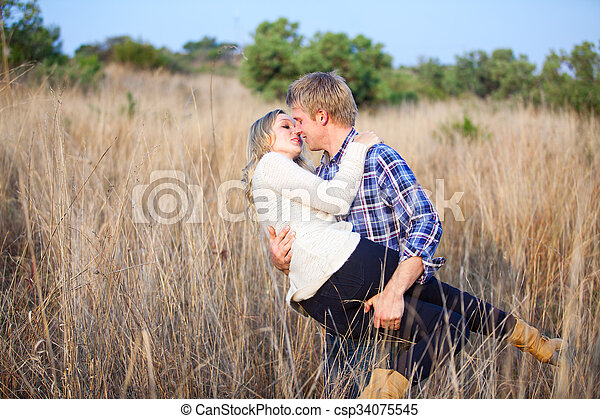 Young man playfully picking up his girlfriend for a kiss - csp34075545