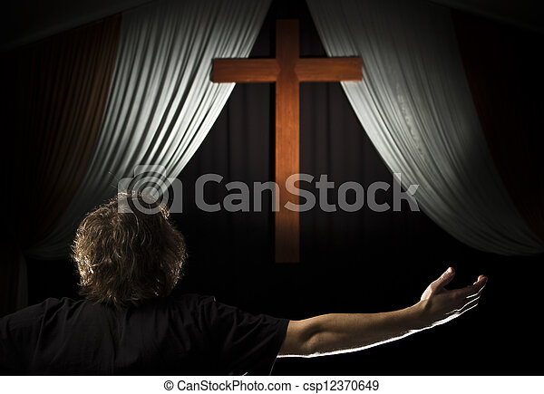 Young man prays before a cross - csp12370649