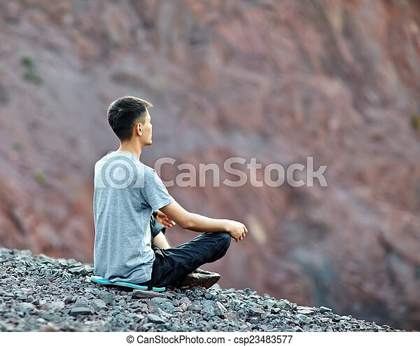 Young man relaxing on rocky cliff  - csp23483577