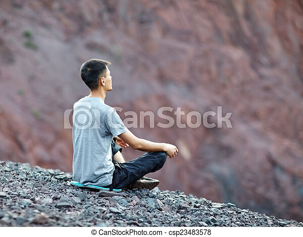 Young man relaxing on rocky cliff  - csp23483578