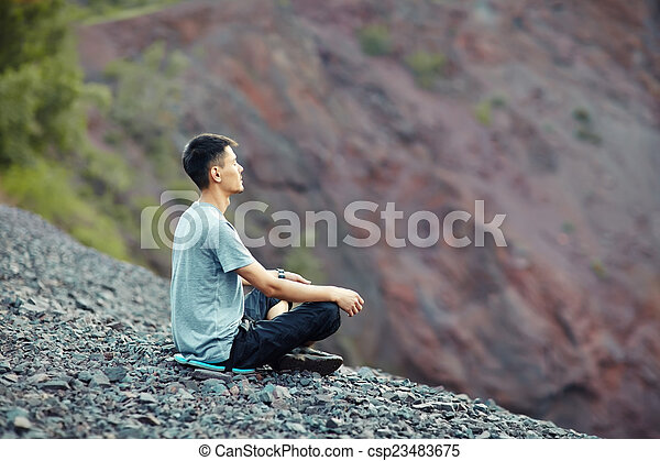 Young man relaxing on rocky cliff  - csp23483675