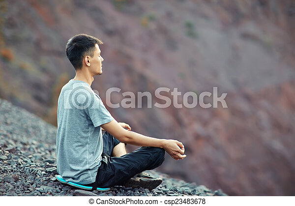 Young man relaxing on rocky cliff  - csp23483678