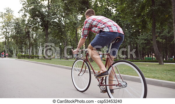 Young man riding vintage bicycle at the park alley  Sporty guy cycling  outdoor  Healthy active lifestyle  Rear Back view Close up Slow motion