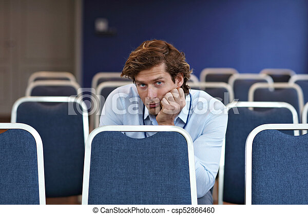 Young man sitting alone in conference room - csp52866460