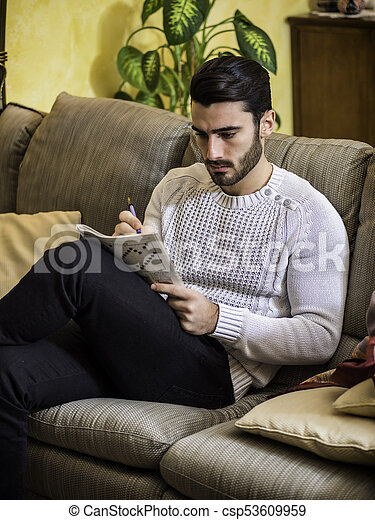 Young Man Sitting Doing A Crossword Puzzle Looking Thoughtfully At A Magazine With His Pencil To His Mouth As He Tries To Canstock