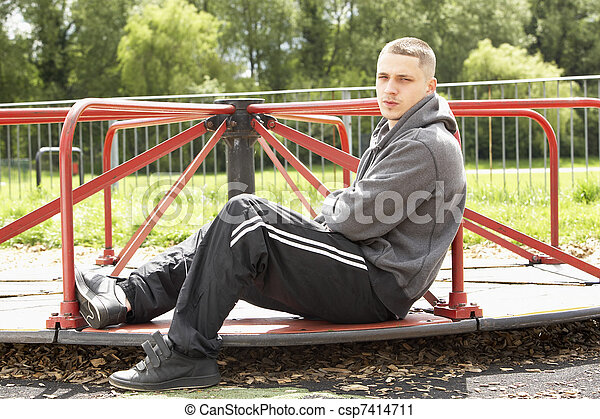 Young Man Sitting In Playground - csp7414711