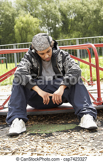Young Man Sitting In Playground - csp7423327