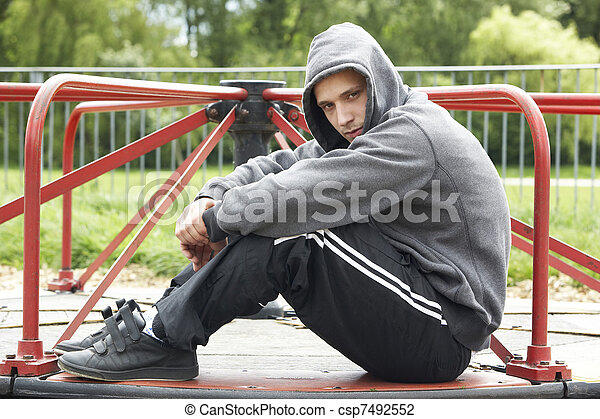 Young Man Sitting In Playground - csp7492552