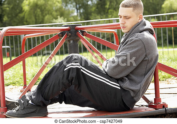 Young Man Sitting In Playground - csp7427049