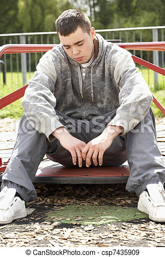 Young Man Sitting In Playground - csp7435909
