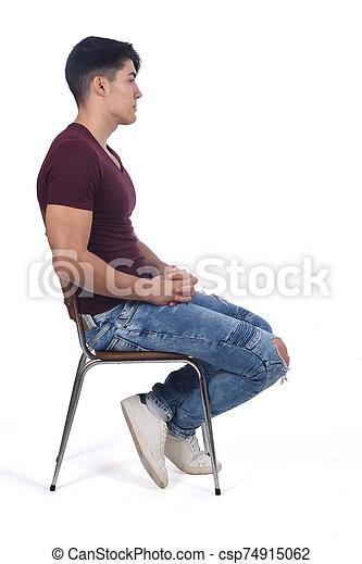 Young man sitting on a chair isolated on white - csp74915062
