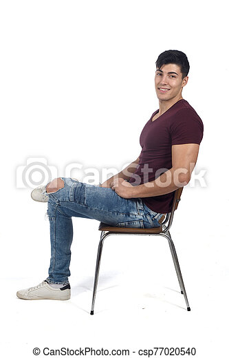 Young man sitting on a chair isolated on white - csp77020540