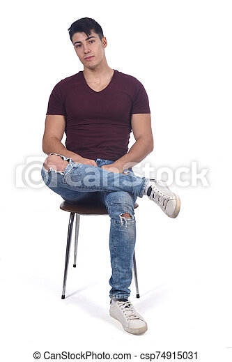 Young man sitting on a chair isolated on white - csp74915031