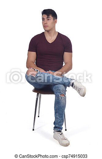 Young man sitting on a chair isolated on white - csp74915033