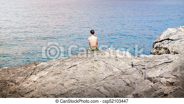 young man sitting on a cliff - csp52103447