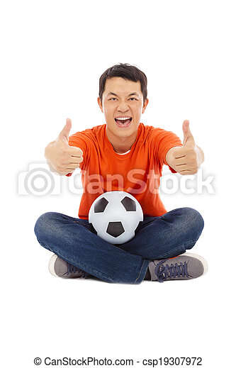 young man sitting with a soccer and thumb up - csp19307972