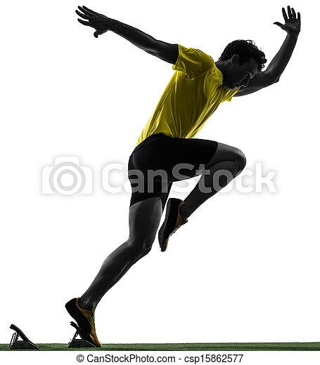 young man sprinter runner in starting blocks silhouette - csp15862577