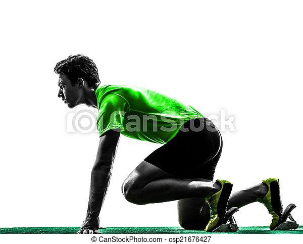 young man sprinter runner in starting blocks silhouette - csp21676427